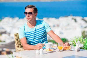 Young guy having breakfast at outdoor cafe with amazing view on Mykonos town.Man drinking coffee on luxury hotel terrace