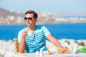 Tourist man having breakfast with coffee at outdoor cafe with amazing view on Mykonos town.