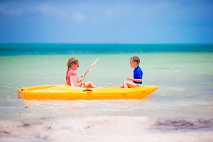 Little girls kayaking in turquoise water in the sea alone