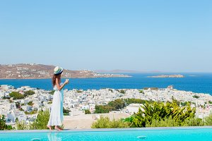 Beautiful woman relaxing on the edge of pool with amazing view of old greek village