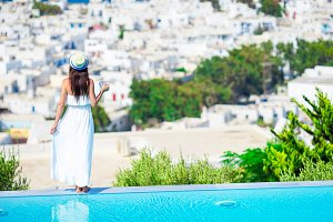 Back view of young girl relaxing on the edge of pool with amazing view on Mykonos, Greece