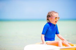 Adorable little girl kayaking and having fun on the beach vacation