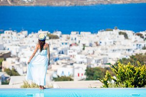 Happy girl feel freedom relaxing on the edge of pool with amazing view on Mykonos, Greece