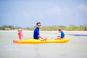 Young father and two little kids kayaking at the sea