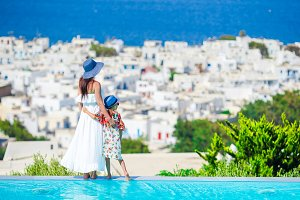 Adorable little girl and young mother in outdoor swimming pool background Mykonos town on Cyclades, Greece