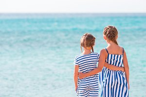 Back view of two girlson the beach background blue sea