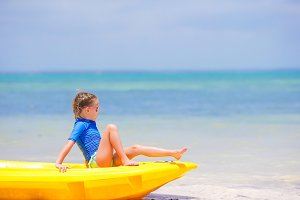Adorable little girl kayaking on the beach vacation