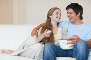 Charming couple watching television while eating popcorn