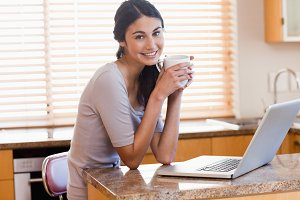 Charming woman using a laptop while drinking a cup of a coffee
