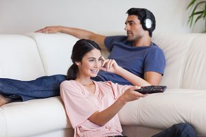 Woman watching TV while her boyfriend is listening to music