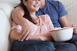 Portrait of a happy couple watching television while eating popcorn