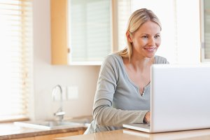 Smiling woman typing on her laptop
