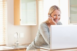 Smiling woman on the phone looking at her laptop