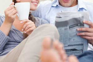 Portrait of a smiling couple reading a newspaper in the morning