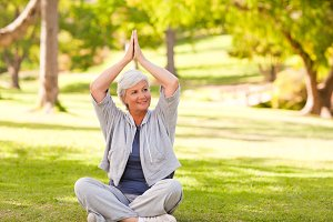 Mature woman practicing yoga in the park