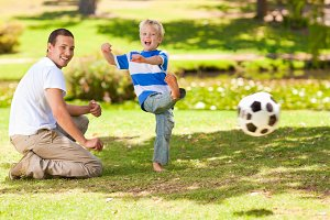 Father playing football with his son during the summer