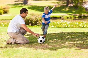 Father playing football with his son in a park