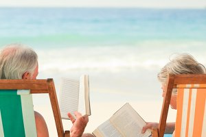 Eldery couple reading at the beach