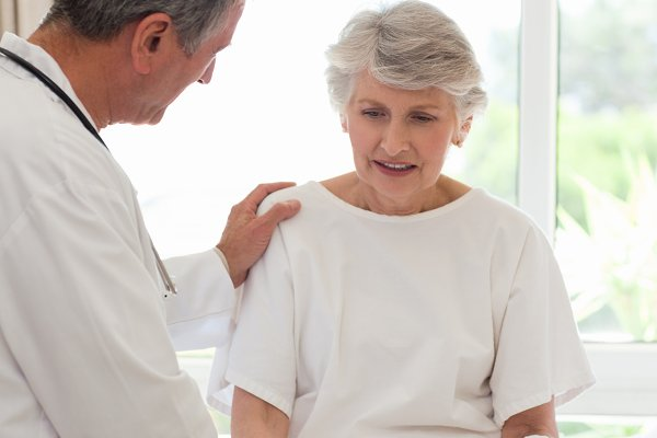 Mature doctor talking with patient
