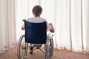 Mature woman in her wheelchair with her back to the camera at home
