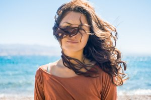 Portrait of happy smiling young woman on beach and sea background. Wind plays with girl long hair