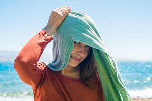 Portrait of young woman with long green scarf on head on the beach with sea background