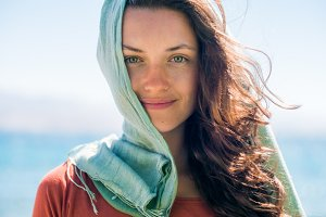 Portrait of happy smiling young woman with long hair and green scarf on the beach and sea background