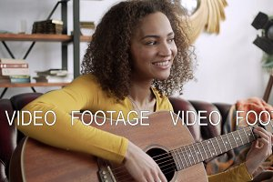 inspired happy young beautiful latin woman play melody on acoustic guitar and beat rhythm