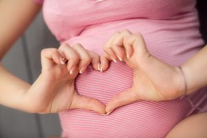 Pregnant Woman holding her hands in heart shape on baby bump.