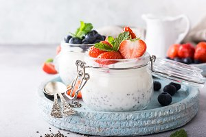 Chia pudding with berries in glass jar.