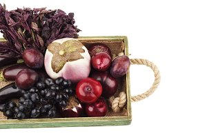 Mix of different violet raw vegetables on the wooden tray, isolated