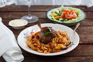 Braised Rabbit Leg in Tomato Sauce with Homemade pasta, dark rustic background