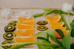 Orange slices and Kiwi fruit on wood background