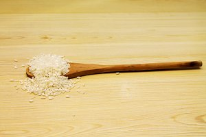 Wooden spoon with rice on wooden background