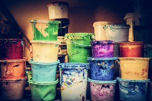 Buckets of liquid paint standing in a workshop.