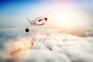 Passenger airplane flying at sunset, blue sky.