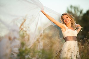 Charming bride stands on the field