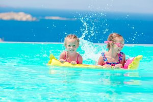 Adorable little girls playing in outdoor swimming pool with beautiful view