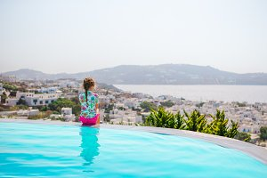 Adorable little girl on the edge of outdoor swimming pool with beautiful view