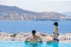 Happy young romantic family enjoy the view on the edge of swimming pool