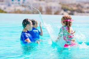 Little kids and happy father having fun in outdoors swimming pool