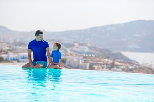 Little girl and happy father having fun on the edge of swimming pool