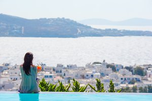 Back view of young woman relaxing on the edge of pool with amazing view on Greece