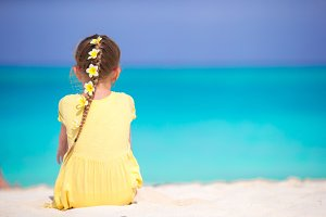 Adorable little girl with frangipani flowers in hair on beach