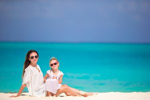 Mother and daughter enjoying time at tropical beach in caribbean vacation