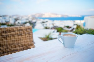 Coffe on the table on summer empty openair cafe with sea view