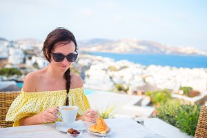 Beautiful woman on breakfast at outdoor cafe with amazing view. Girl enjoy her hot coffee early in the morning