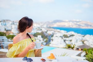 Beautiful woman having breakfast at outdoor cafe with amazing view. Girl enjoy her hot coffee early in the morning