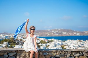Little girl outdoors background famous village on Mykonos Island, in Greece