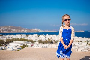 Little girl in blue dress outdoors. Kid at street of typical greek traditional village on Mykonos Island, in Greece